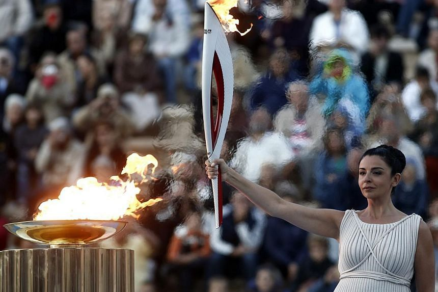 Greek actress Ino Menegaki, playing the role of high priestess, raises an Olympic torch for the Sochi 2014 Winter Games during a handover ceremony at the Panathenean stadium in Athens October 5, 2013. The Olympic torch was formally handed over from G
