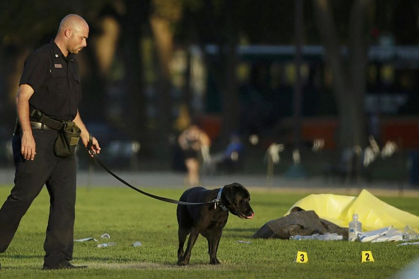A law enforcement officer uses a police dog to search for evidence at the scene where a man set himself on fire within sight of the U.S. Capitol building on the U.S. National Mall in Washington, October 4, 2013. A man who set himself on fire on the N