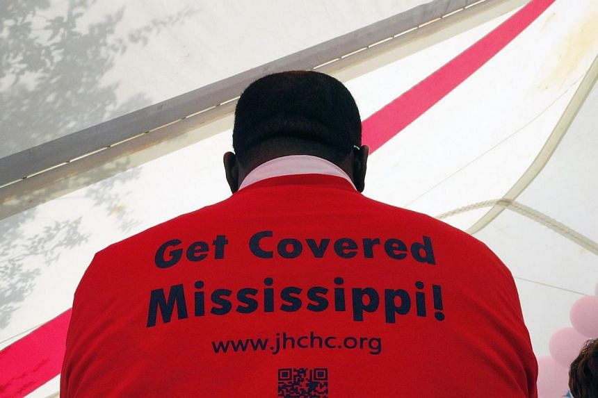 """Supporters of the Affordable Care Act, widely referred to as """"Obamacare"""", gather outside the Jackson-Hinds Comprehensive Health Center in Jackson, Mississippi October 4, 2013.With their leadership clinging to its strategy of demanding cha"""