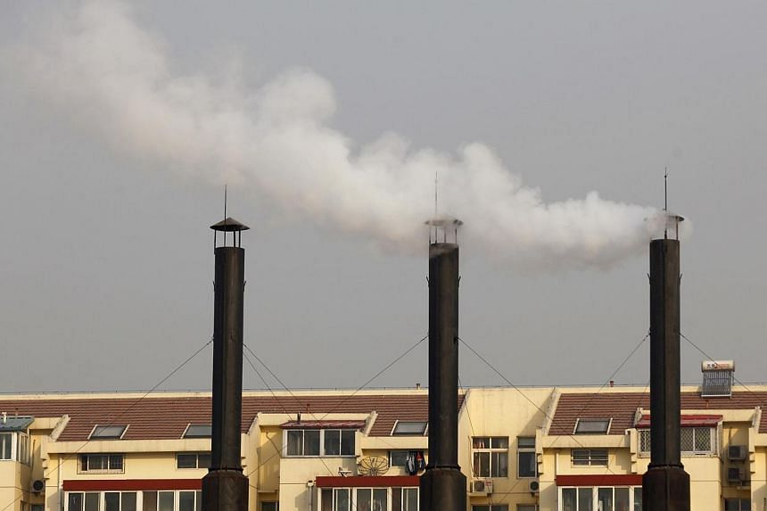 Smoke billows from the chimneys of a heating plant near a residential compound in Beijing, in this November 23, 2010 file photo. A cloud of pollution descended over Beijing at the weekend, shrouding the city and its famous cultural landmarks in a thi