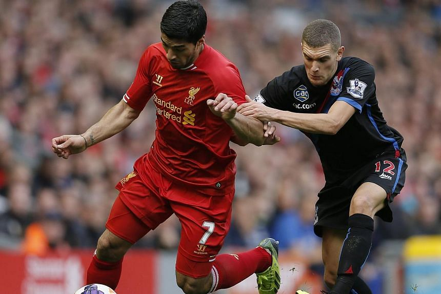 Liverpool's Luis Suarez (L) challenges Crystal Palace's Stuart O'Keefe during their English Premier League soccer match at Anfield in Liverpool, northern England October 5, 2013. Liverpool striker Luis Suarez made a goal-scoring return to Anfield as