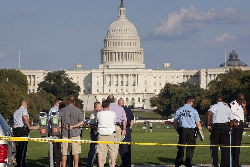 Law enforcement officers are near the scene on the National Mall in Washington, where, according to a fire official, a man set himself on fire on Friday, Oct 4, 2013. A man who set himself on fire on the National Mall in the US capital has died