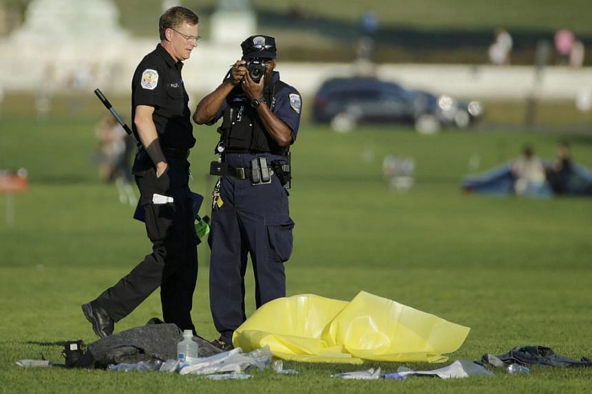 Police officers investigate the scene where a man set himself on fire in front of the US Capitol building on the US National Mall in Washington, on October 4, 2013. A man who set himself on fire on the National Mall in the US capital has died,
