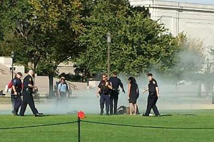 First responders and people assist a man who apparently set himself on fire at the National Mall in Washington, on Oct 4, 2013 handout photo by Vanessa Sink.A man who set himself on fire on the National Mall in the US capital has died, police s
