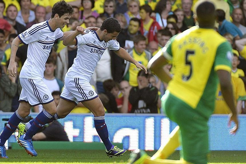 Chelsea Eden Hazard (centre) celebrates scoring with teammate Oscar (left) against Norwich City during their English Premier League soccer match at Carrow Road in Norwich, Oct 6, 2013.Hazard and Willian came off the bench and scored as Chelsea