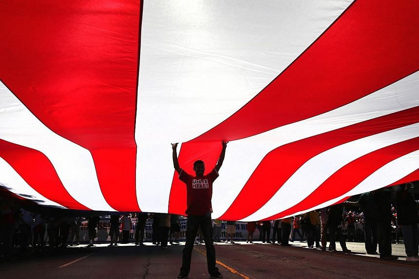 Immigration advocates support an American flag while taking part in a National Day of Dignity and Respect march on Oct 5, 2013 in Los Angeles, California. Thousands of people poured into streets across the United States on Saturday in a push to