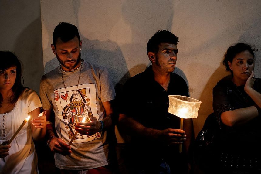 People take part in a torchlight procession in memory of the victims of the shipwreck on Oct 4, 2013 on the Italian island of Lampedusa. Survivors cried over the coffins of their loved ones on Saturday as Italy denied claims that rescue efforts were