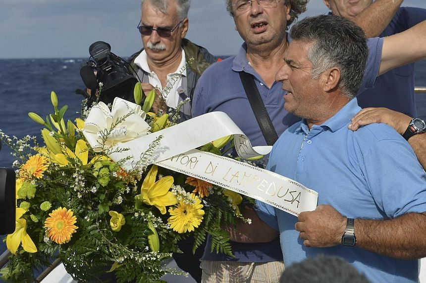 """Fishing boat captain Calosero Spalma, right, throws a wreath, with writing on a ribbon written in Italian """"Fishermen of Lampedusa"""", into the sea to pay tribute to the victims of Thursday's migrant shipwreck off the coast of the southern Italian islan"""