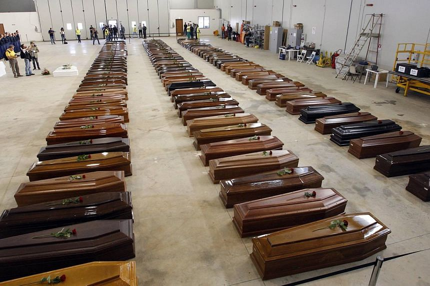 Coffins of victims from a shipwreck off Sicily are seen in a hangar of the Lampedusa airport on Oct 5, 2013. Survivors cried over the coffins of their loved ones on Saturday as Italy denied claims that rescue efforts were delayed in a shipwreck trage