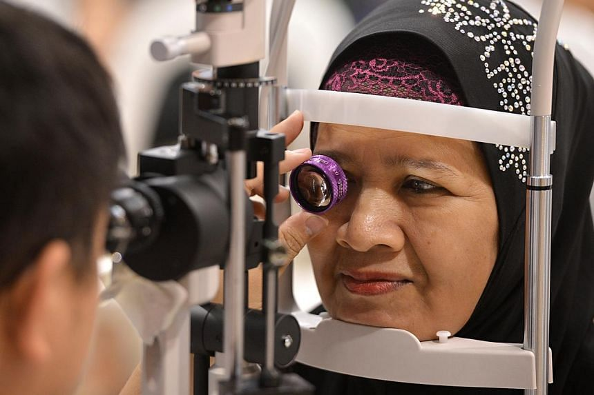 More than 600 Bedok residents, including Madam Safiah Binte Ismail (right), participated in a free eye screening session on Sunday morning, in conjunction with Lions World Sight Day. -- ST PHOTO: NURIA LING