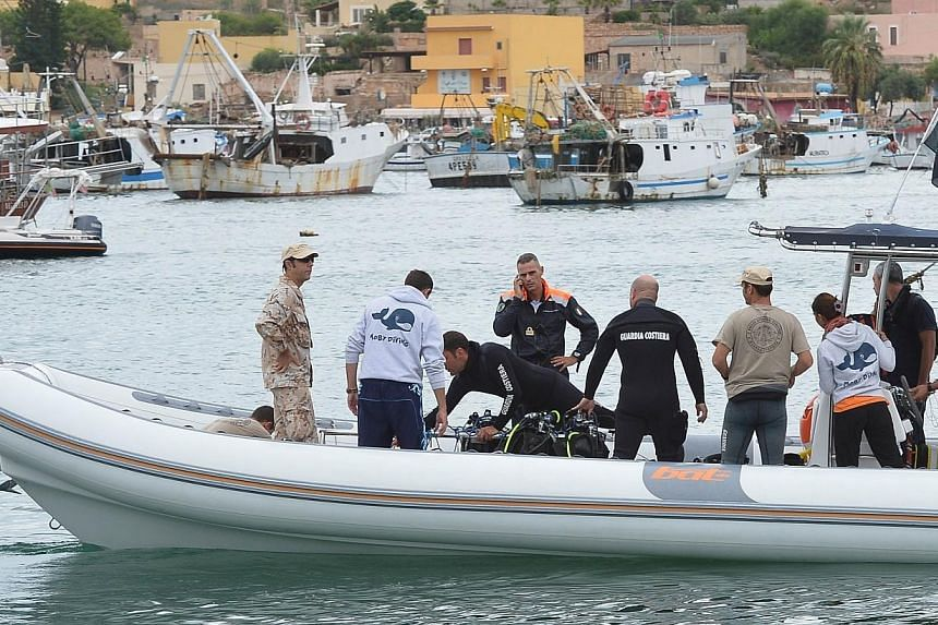A team of divers with coast guards' members leaves the Lampedusa harbour on Oct 6, 2013 before operations to recover bodies from the shipwreck that sank on Oct 4, 2013.Divers in Italy recovered 16 more bodies on Sunday after a shipwreck in whic