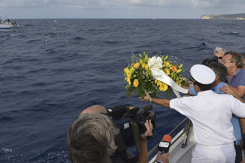 Fishing boat captain Calosero Spalma, wearing white, throws a wreath into the sea to pay tribute to the victims of Thursday's migrant shipwreck off the coast of the southern Italian island of Lampedusa, Saturday, Oct 5, 2013. -- PHOTO: AP