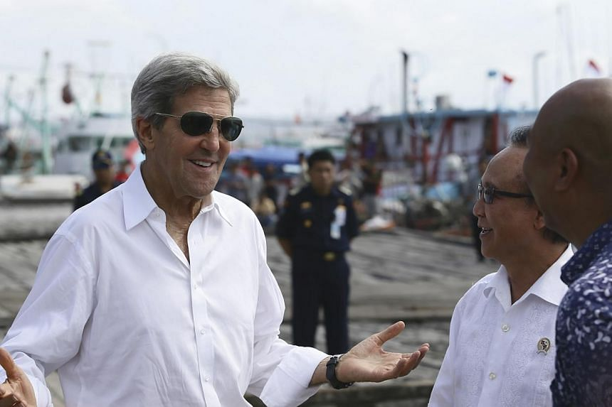 US Secretary of State John Kerry speaks to officials during a visit to a tuna packaging factory in Bali, Indonesia, Sunday, Oct 6, 2013. Mr Kerry on Sunday said two high-profile raids in Libya and Somalia showed the United States' unflinching de