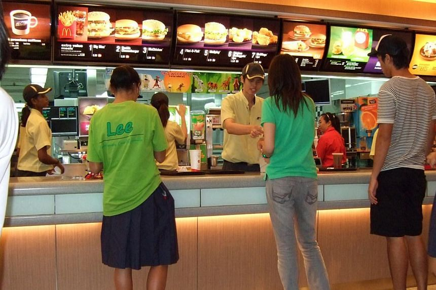 McDonald's employees serving customers at the counter July 6, 2009. Students with special needs will now have a chance to get some work experience. Fast-food chain McDonald's launched a work attachment programme on Monday in collaboration with Moveme