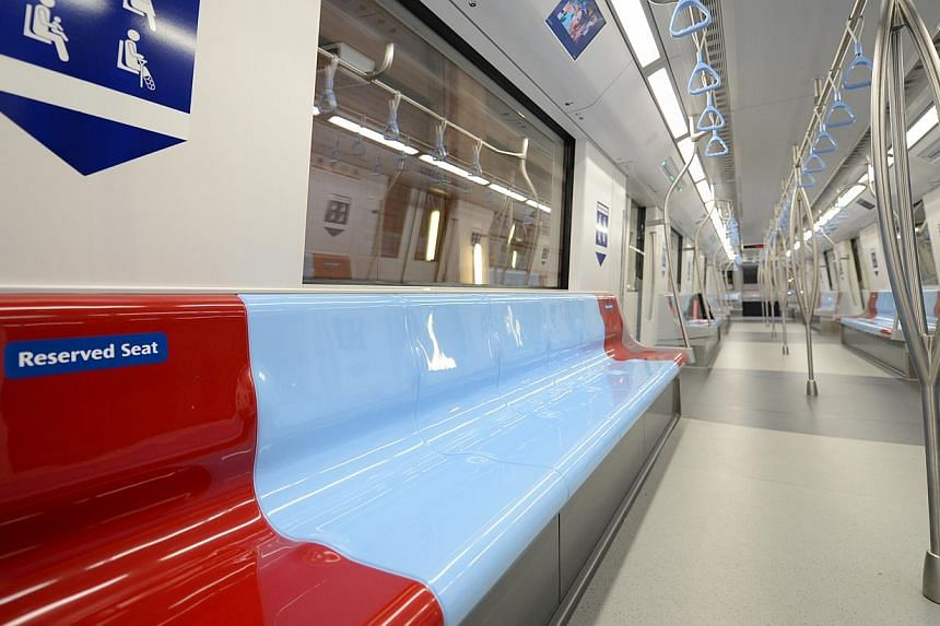 The interior of the new Downtown Line trains, which are fully automatic and driverless. The reserved seats are in red to highlight the fact that they are meant for passengers with special needs.The first stage of the Downtown Line will open on