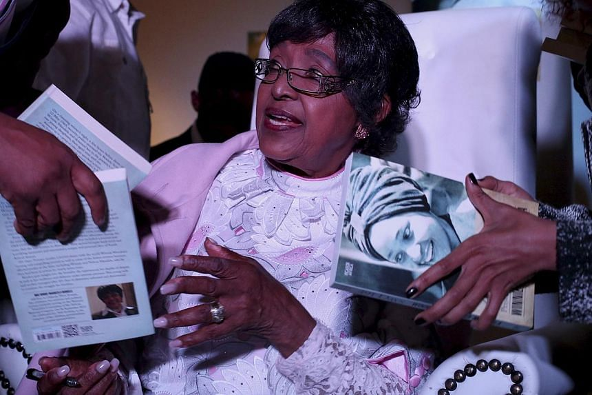 Winnie Madikizela-Mandela, ex-wife of former South African President Nelson Mandela, is given copies to sign during a celebratory event around the release of her book titled 491 Days in Johannesburg August 8, 2013.Ailing global peace icon Nelso