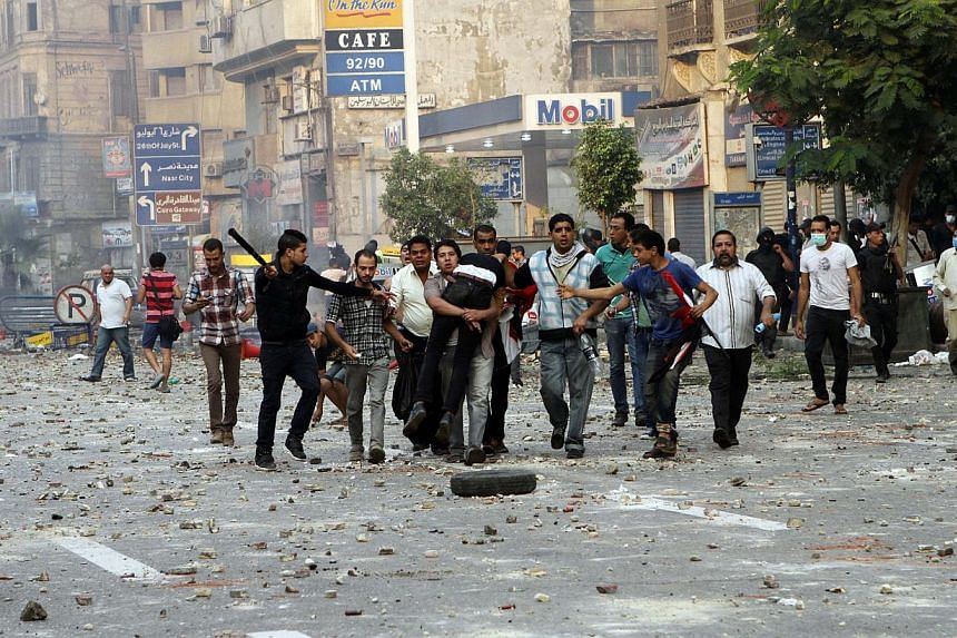 Egyptian security forces and civilians detain a supporter of ousted Egyptian President Mohammed Morsi near Ramsis Square, Cairo, Egypt. At least 50 people were killed in clashes between Islamists and police in Egypt on Sunday, as thousands of the mil