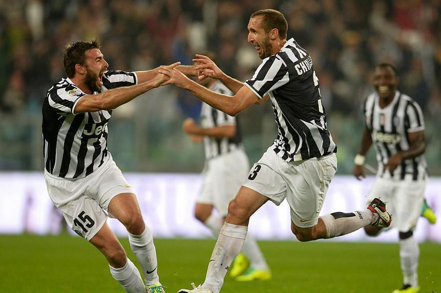 Juventus' defender Giorgio Chiellini (right) and Juventus' defender Andrea Barzagli celebrate after scoring during the Serie A football match Juventus vs AC Milan on Oct 6, 2013 in Turin. Champions Juventus overcame conceding a first-minut