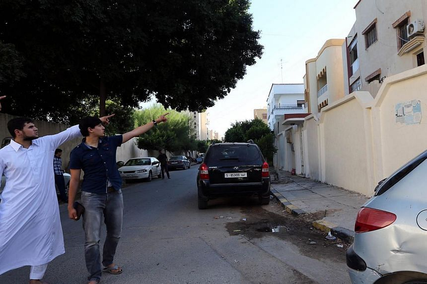 Mr Abdullah al-Raghie (left) and Mr Abdul Moheman al-Raghie (second left), the sons of al-Qaeda suspect Abu Anas al-Libi, point at the house next to the scene where their father was kidnapped by US special forces in a commando raid in Nofliene, 5km f