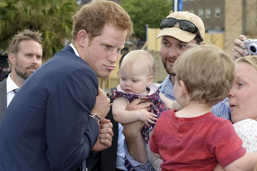 Prince Harry makes a funny face at a young child as he is greeted by a large crowd during the International Fleet Review in Sydney, Saturday, Oct 5, 2013. -- FILE PHOTO: AP