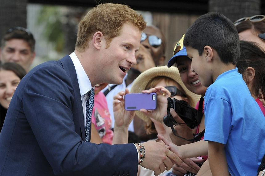 Prince Harry shakes hands with a small boy as he is greeted by a large crowd during the International Fleet Review in Sydney, Saturday, Oct 5, 2013. Another royal wedding may soon be on the cards for Britain if Prince Harry has finally managed to get