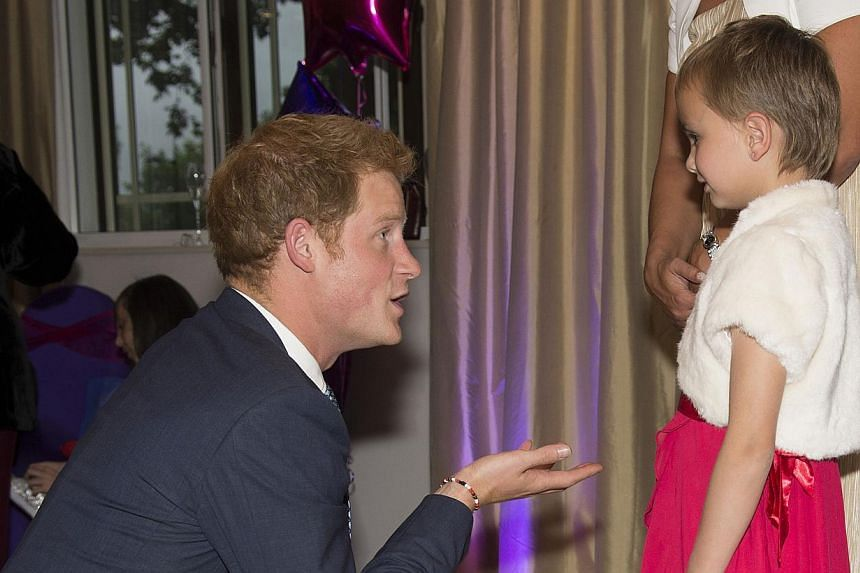 Britain's Prince Harry (left) talks with Maidison Kirk, 6, as he attends the annual WellChild awards in central London on Sept 11, 2013. -- FILE PHOTO: AFP