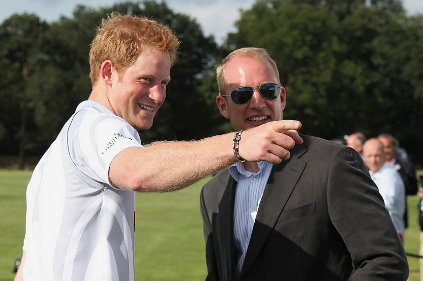 Britain's Prince Harry (left) gestures after competing in a charity polo match at Coworth Park, southern England Aug 3, 2013. -- FILE PHOTO: AFP