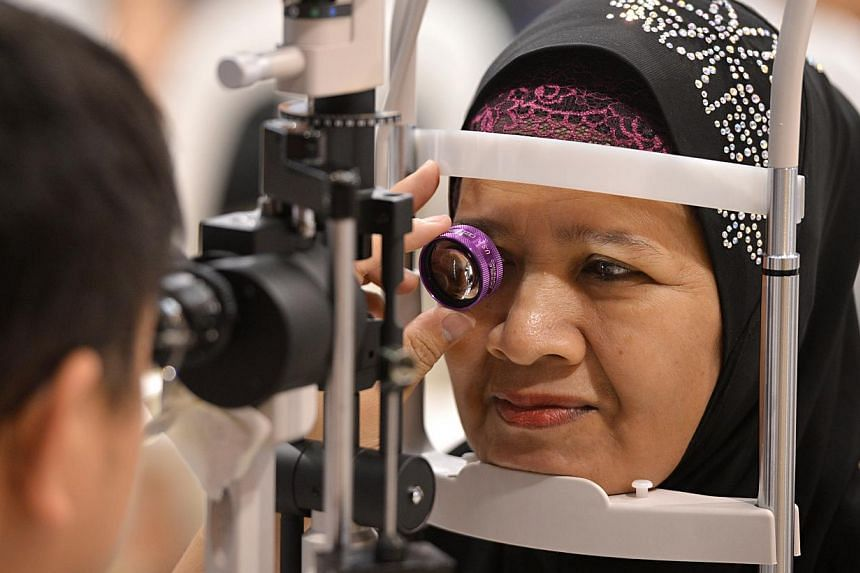 Madam Safiah Ismail, 62, getting her eyes examined during a community event held yesterday at the Eunos Community Club, where more than 600 residents received free eye checks. ST