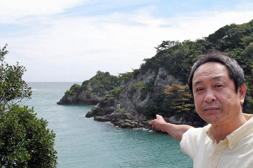 Taiji town assemblyman Hisato Ryono shows a cove where dolphin hunting takes place in Taiji, in Wakayama prefecture, western Japan on Sept 7, 2009.The Japanese town made infamous by the Oscar-winning documentary The Cove will open a marine park