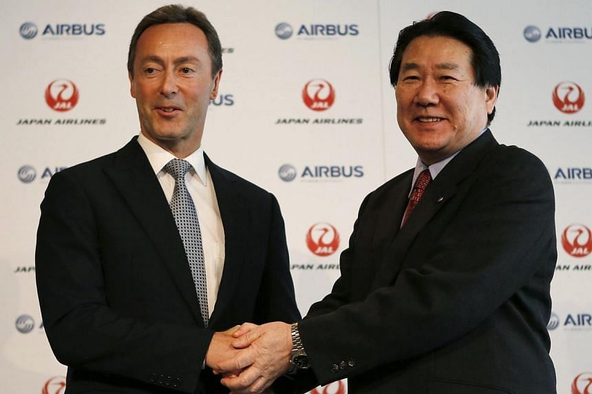 Japan Airlines President Yoshiharu Ueki (right) shakes hands with Airbus Chief Executive Fabrice Bregier during their joint news conference in Tokyo on Monday, Oct 7, 2013. Japan Airlines said on Monday it is ordering 31 Airbus A350 planes in a deal
