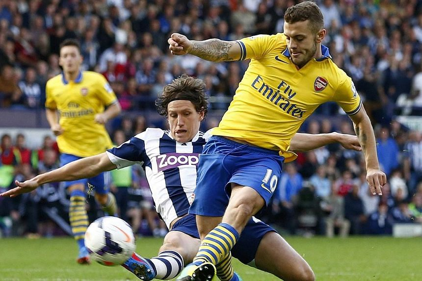 Arsenal's Jack Wilshere (right) is challenged by West Bromwich Albion's Billy Jones during their English Premier League soccer match at The Hawthorns in West Bromwich, central England, Oct 6, 2013. Arsenal moved back to the top of the Premier League