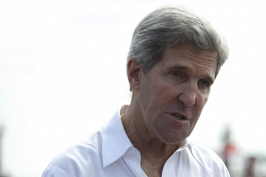 US State Secretary John Kerry speaks to the media during a visit to a tuna packaging factory in Bali, Indonesia, Sunday, Oct 6, 2013. Mr Kerry said on Sunday that a pair of US military raids against militants in North Africa sends the message that te
