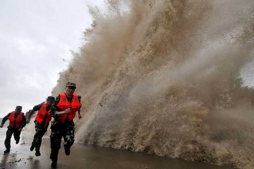 A huge wave hits the dike as guards run along it as Typhoon Fitow moves to make its landfall in Wenling, east China's Zhejiang province on Oct 6, 2013. Typhoon Fitow slammed into the east coast of China on Monday after thousands of people were evacua