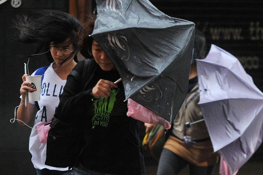 Pedestrians walk through strong winds and rain caused by Typhoon Fitow in Taipei on Oct 6, 2013. -- PHOTO: AFP