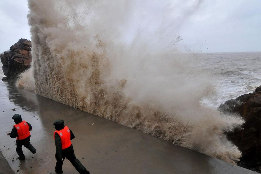 A huge wave hits the dike as guards run along it Typhoon Fitow moves to make its landfall in Wenling, east China's Zhejiang province on Oct 6, 2013. -- PHOTO: AFP