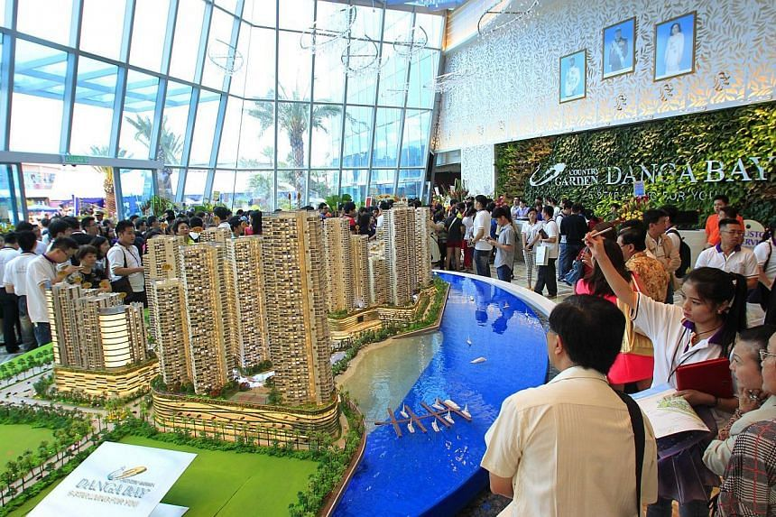 Prospective buyers viewing the model of Country Garden Danga Bay during its Grand Opening Ceremony in Johor Bahru on Aug 11, 2013. Malaysia's southern state of Johor, which neighbours Singapore, will impose a higher processing fee on foreigners who b