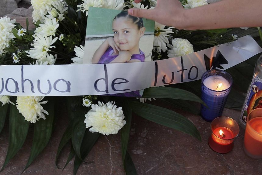 A relative arranges a photograph of a girl during a candlelight vigil for the victims of a monster truck that ploughed into a crowd of spectators during a show at El Rejon park, on the outskirts of Chihuahua, on Oct 6, 2013. Chihuahua governor Cesar