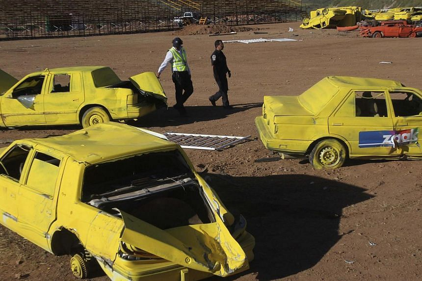 Police officers walk past scrap cars, part of the show where a monster truck ploughed into a crowd of spectators at El Rejon park, on the outskirts of Chihuahua, on Oct 6, 2013. Chihuahua governor Cesar Duarte said the driver of the monster truck per