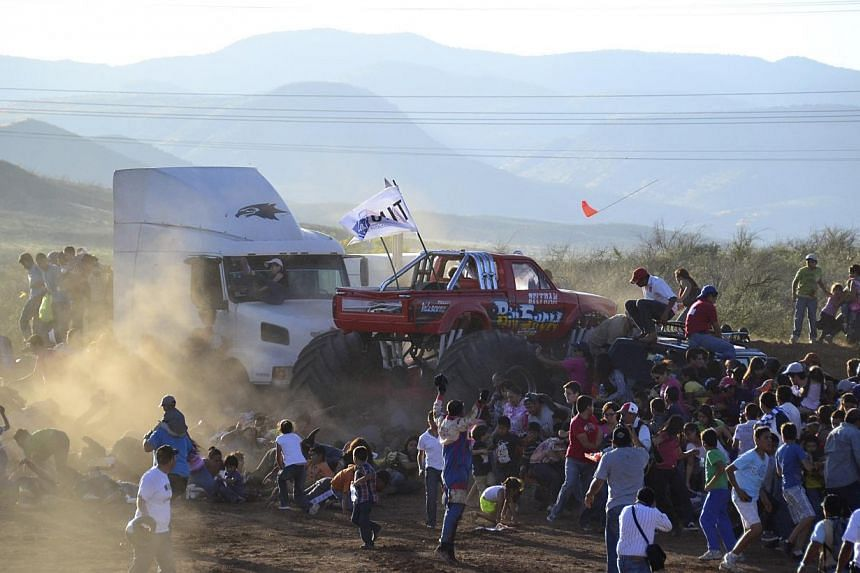 People run as an out of control monster truck plows through a crowd of spectators at a Mexican air show in the city of Chihuahua, Mexico, Saturday Oct. 5, 2013.The driver of a monster truck that ran over spectators in northern Mexico had perfor