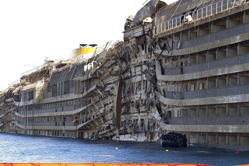 A side of the Costa Concordia is seen on the Tuscan island of Giglio, Italy on Sept 18, 2013, after the crippled cruise ship was pulled completely upright from its side where it capsized last year.Italian rescuers have found human remains on th