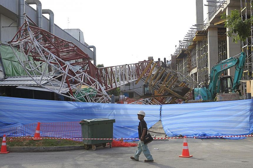 A crane was reduced to twisted metal after it toppled over at a construction site in Hougang on Tuesday, Oct 8, 2013.-- ST PHOTO: KEVIN LIM