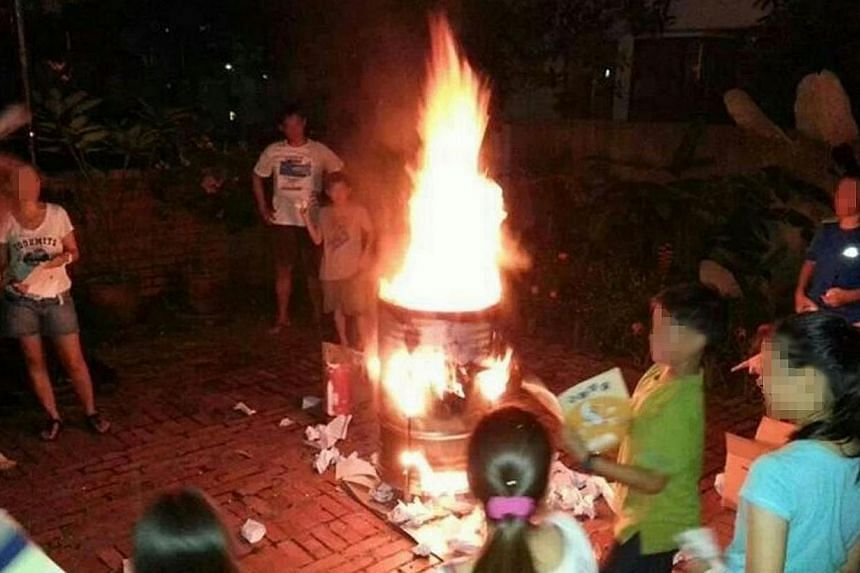 In this picture that was initially published in Shin Min Daily News, a group of children and parents appear to be burning textbooks following the recent PSLE.  The photo later made its rounds on Facebook, sparking complaints over the message it sent