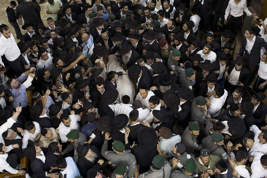 Ultra-Orthodox Jewish men gather near the body of Rabbi Ovadia Yosef, the spiritual leader of the ultra-religious Shas political party, before his funeral at a seminary in Jerusalem, Oct 7, 2013. Rabbi Yosef died on Monday at the age of 93. -- PHOTO: