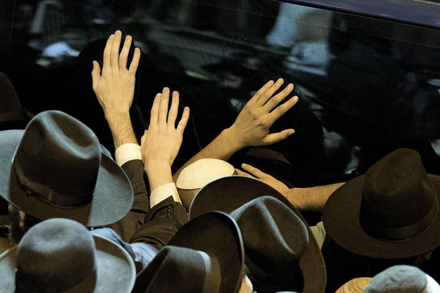 Ultra-Orthodox Jewish mourners touch the vehicle transporting the body of Rabbi Ovadia Yosef, the spiritual leader of the ultra-religious Shas political party, during his funeral in Jerusalem on Oct 7, 2013. Rabbi Yosef died on Monday at the age of 9