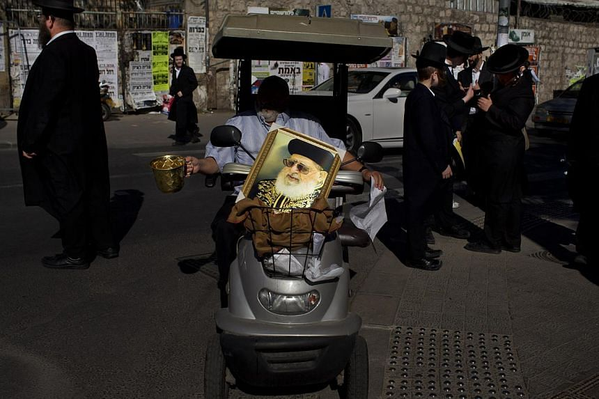 An Israeli man carries a picture of the late Rabbi Ovadia Yosef while he begs for money outside a yeshiva during Ovadia's funeral, in Jerusalem, on Oct 7, 2013. Rabbi Yosef died on Monday at the age of 93. -- PHOTO: AP