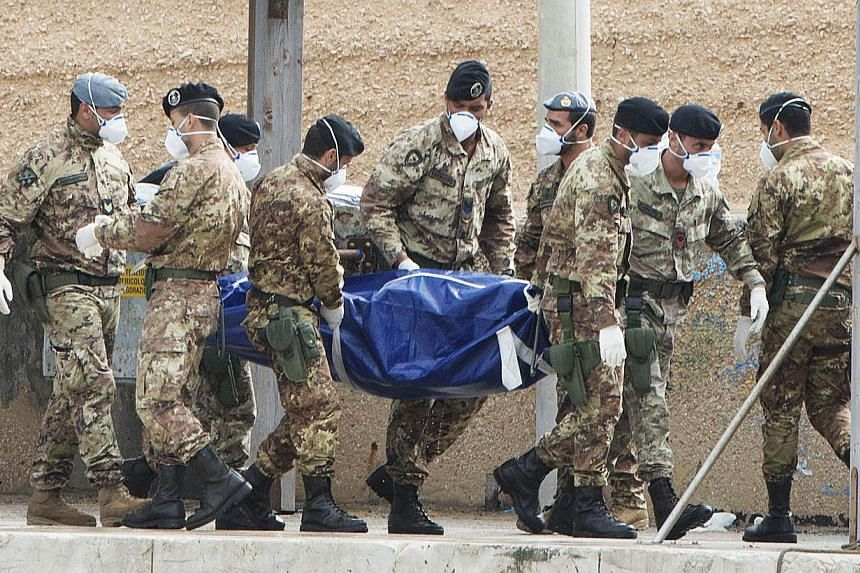 Italian soldiers carry the body of a victim from the shipwreck of Oct 3, 2013 as divers recovered 17 more bodies today on Oct 7, 2013 in the Lampedusa harbour. Divers in Italy recovered 38 more bodies on Monday from a shipwreck in which over 300 Afri