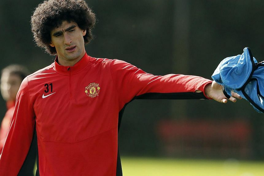 Manchester United's Marouane Fellaini throws a training bib during a training session at the club's Carrington training complex in Manchester on Sept 16, 2013.Belgium midfielder Marouane Fellaini will wear a wrist splint in his country's final
