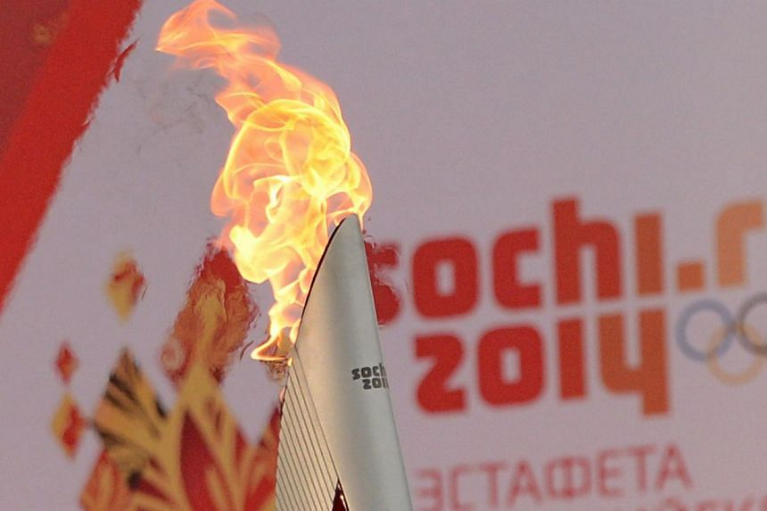 One of the Olympic torches rises in front of a poster with the Sochi 2014 Winter Olympic logo just outside the Red Square in Moscow, on October 7, 2013, during a ceremony to kick off the Sochi 2014 Winter Olympic torch relay across Russia. Russi