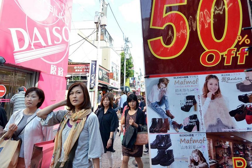 Shoppers walk past displays offering clothing on sale in Tokyo's Harajuku shopping district on Sept 27, 2013. Bank of Japan policy board members agreed that a virtuous cycle spanning from production to income to spending is functioning well as the ec