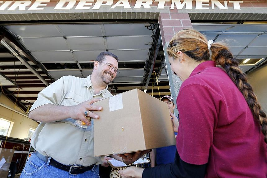 Volunteer David Cole, left, hands Richard Contreras a box of donated food, Tuesday, Oct 8, 2013, in Tusayan, Arizona. Americans are fed up with the political deadlock in Washington and frustrated with how the federal government shutdown is interferin